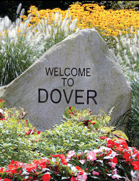 Large rock surrounded by flowers with welcome to Dover engraved on it